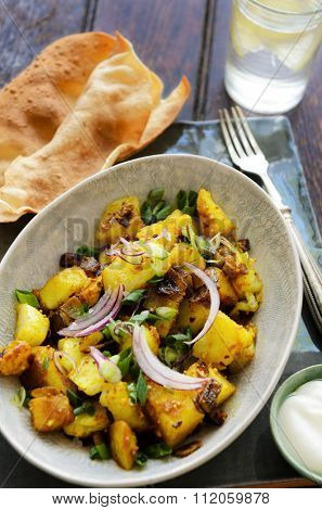Curry potatoes cooked in asian south indian spices like turmeric and mustard seeds, an elegant ethnic dish served with poppadoms and yoghurt