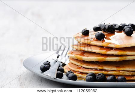 Pancakes with fresh blueberries and maple syrup, plenty of copy space