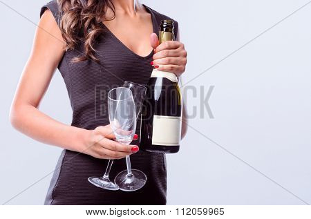 Anonymous woman holding a bottle of champagne sparkling wine and two glasses for party celebration