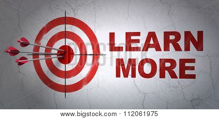 Learning concept: target and Learn More on wall background
