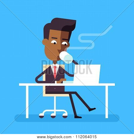 Man sitting at desk with laptop and hot beverage.