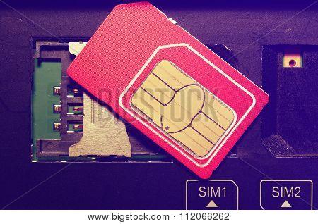 Red SIM card on slots in mobile phone.