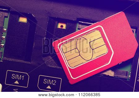 Red SIM card on slots in mobile phone.