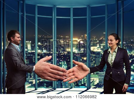 Businesswoman and businessman are going to handshake in the office