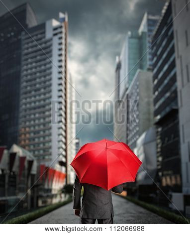 Businessman is standing back with a red umbrella in the city