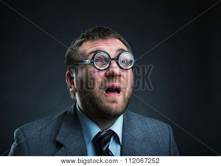 Surprised nerd businessman in glasses over grey
