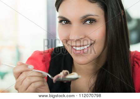 Beautiful girl eating fresh delicious calamari cebiche