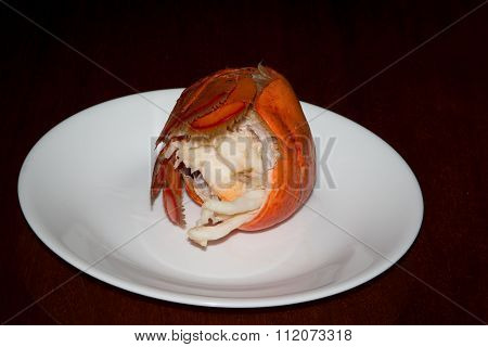 Boiled lobster tail on a small white plate.