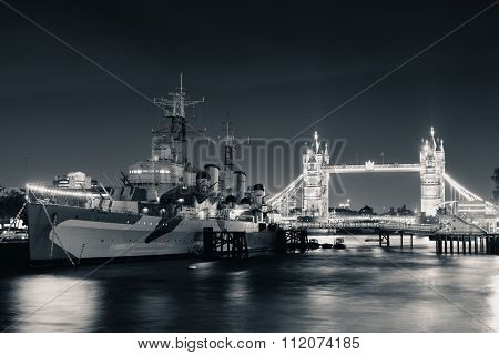 HMS Belfast warship and Tower Bridge at night in Thames River in London