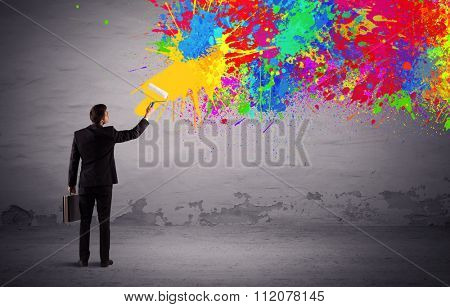 An elegant businessman in suit painting colorful splatter, bright colors on grey urban wall with a paint roller in his hand concept