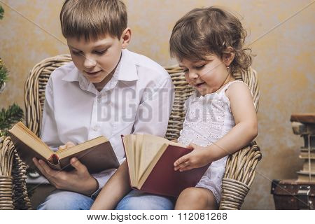 Cute Babies Boy And Girl In A Chair Reading A Book In A Interior