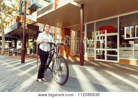 Portrait of happy young female bicyclist riding in city