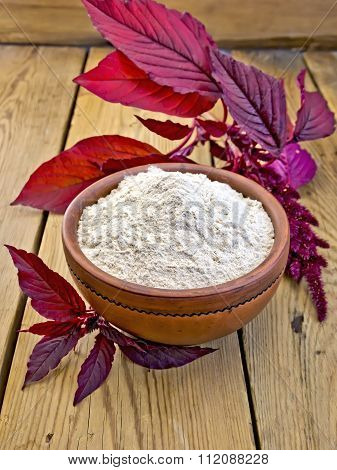 Flour amaranth in clay bowl on board with purple flower