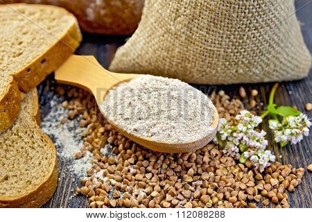 Flour buckwheat in spoon with cereals and flower on board