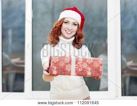 Caucasian Santa Girl Holding Christmas Box Gift. Portrait Of Happy Woman Posing In Santa Hat With Mu
