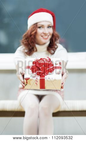 Christmas, New Year, X-mas Concepts And Celebrations. Young Caucasian Santa Helper Girl Offers Prese