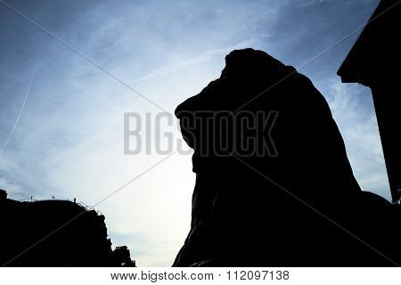 Silhouette of one of the four lions statues that surround Nelson's Column in Trafalgar Square, shot against blue sky.