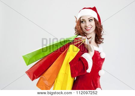New Year And Christmas Concept And Ideas. Smiling Caucasian Red-haired Santa Girl With Shopping Bags