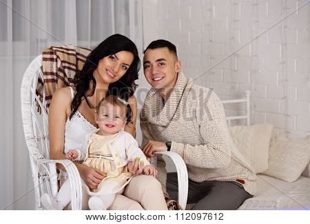 parents with a child on a chair
