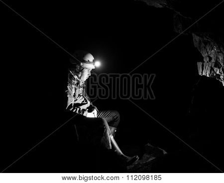 Girl resting in an abandoned mine with light from head torch