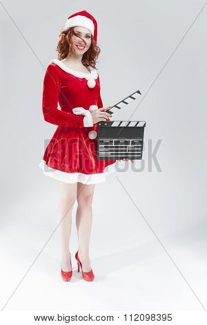 Full Length Portrait Of Sexy Female Santa Girl With Clapperboard Posing Against White Background.