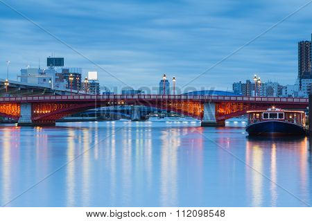 Twilight, Red Bridge over river in Tokyo