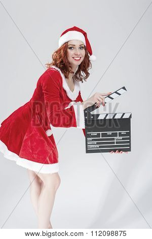 Cinema And Film Production Concept And Ideas. Portrait Of Smiling Female Santa Girl With Clapperboar