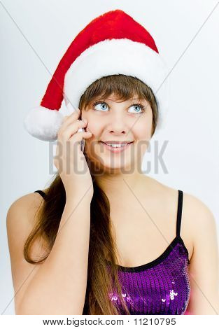 Happy Smiling Girl With Santa Hat With A Phone