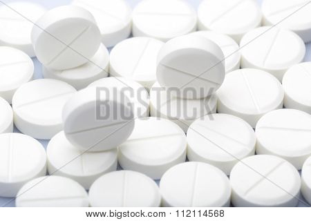 White pills on a white background