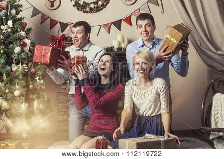 Friends Of Four Men And Women Give Gifts In The Christmas Interior