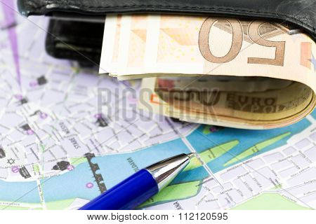 European union currency in a wallet, pen and map