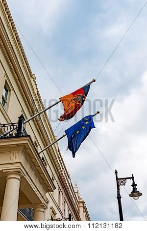 German and European Union flags waving from the German embassy balcony in London exterior view