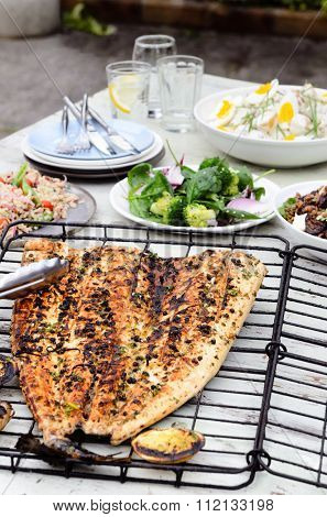 Table full of side dishes, variety assortment of salads with a whole grilled fish for a party gathering in the garden entertaining outdoors