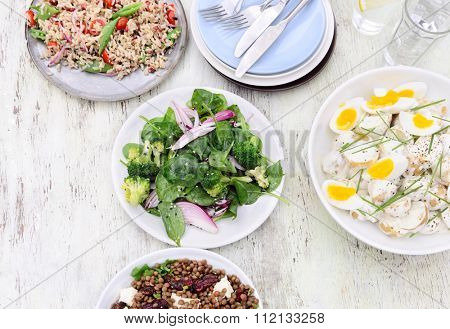Overhead of a variety assortment of side dishes, green salad, brown rice salad, lentil beetroot salad on a rustic background with copy space