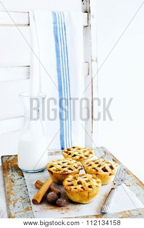 Farmstyle inspired lattice fruit pies presented on a wooden chair with dishcloth and a pitcher of milk