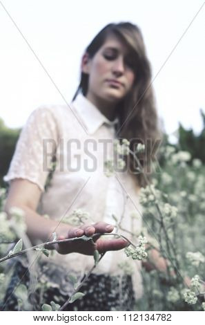 Vintage styled shoot of a young woman in a field, edited in a dreamy nostalgic effect