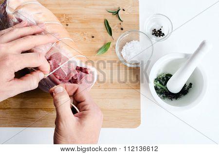Chef hands rolling boneless raw pork shoulder, preparing for cooking roasting