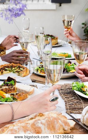 Group of friends holding their wine glasses for a toast at a outdoor garden party with fresh organic platters of food laid out on a table, a casual party gathering