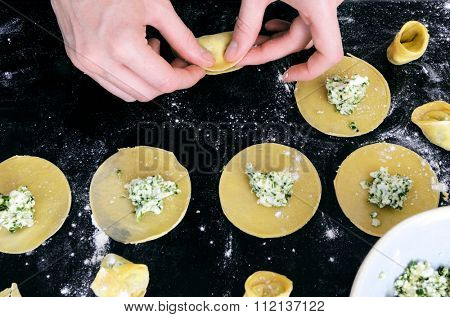 Pair of hands filling tortellini or ravioli with ricotta and spinach herb stuffing , from overhead view