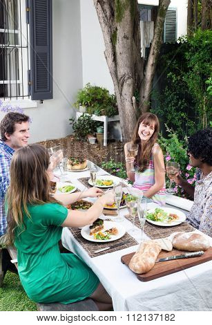 Friends having fun, talking and laughing at a party with food and alcohol, a casual lunch get together in a garden
