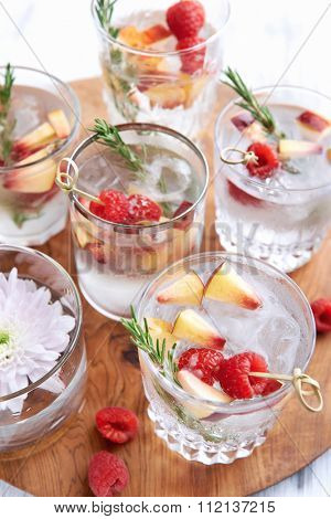 Close up of clear cocktails/soda water being served on a wooden tray decorated with flowers, raspberries, sliced apples and garnish