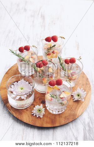 Clear cocktails/soda water being served on a wooden tray decorated with flowers, raspberries, sliced nectarines and garnish