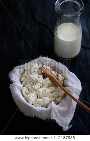 Homemade ricotta cheese draining in muslin cheese cloth with main ingredient milk on dark background