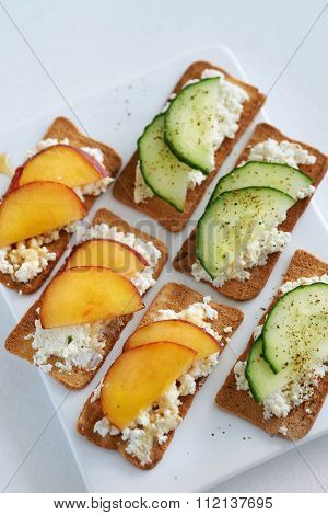 Fresh ricotta cottage cheese healthy snack starter platter appetiser with sliced peach nectarine and cucumber, perfect party canapes