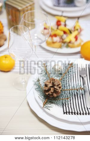White plates with flatware on a Christmas table