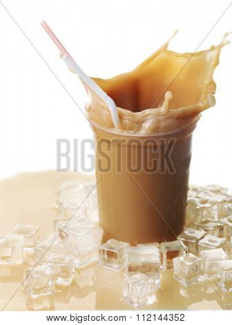 Cup of ice coffee with splashes on table