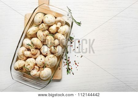 Marinating mushrooms with spices on wooden table