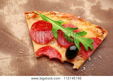 Bitten slice of pepperoni pizza with olives and arugula on cardboard