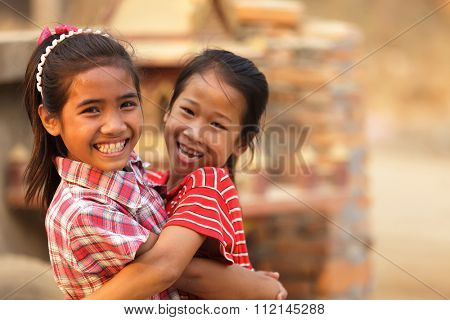 XAYABURI, LAOS, FEBRUARY 16, 2012 : Portrait of a Laotian little girl hugging her sister in the village of Xayaburi, Laos.