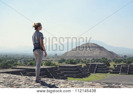 Young Woman Standing On Top Of Pyramid And Overlooking Teotihuacan